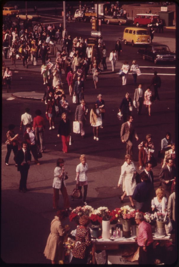 COMMUTERS HEAD FOR HOME AT RUSH HOUR NEAR THE DOCKS OF THE STATEN ISLAND FERRIES IN BATTERY PARK, LOWER MANHATTAN. SOME PAUSE AT A FLOWER-SELLERS' STAND, 05/1973